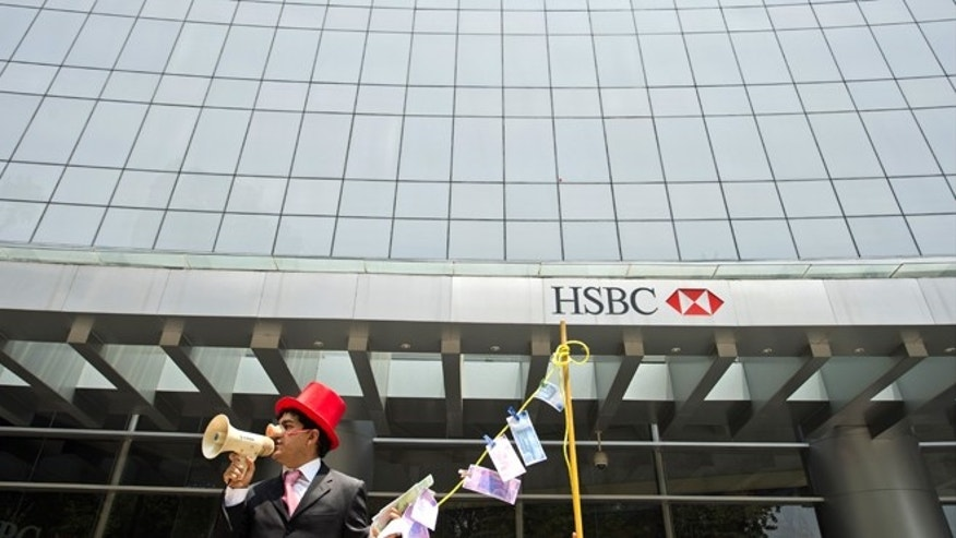 "A man weraing a pig nose and holding fake notes shouts slogans during a protest in front of a HSBC branch building, in Mexico City on July 30, 2012. HSBC said on July 30 it took a provision of 700 USD million (571 million euros) to cover fines for failing to apply anti-money laundering rules and warned the overall cost could be ""significantly higher."" AFP PHOTO/Alfredo ESTRELLA        (Photo credit should read ALFREDO ESTRELLA/AFP/GettyImages)"