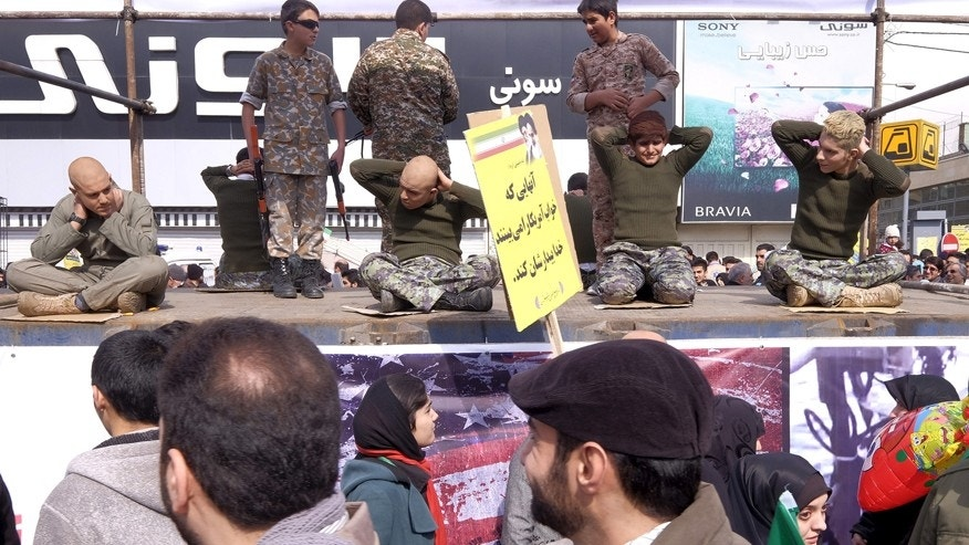 Feb. 11, 2016: Iranian students re-enact a scene from the arrest of American sailors by Iran's Revolutionary Guard, during a ceremony marking the 37th anniversary of the Islamic Revolution, in Tehran.