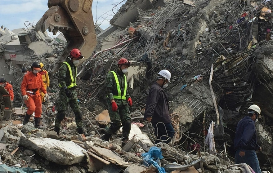 Rescue teams continue to use heavy excavation machinery to dig through the rubble of a collapsed building complex in Tainan, Taiwan, Thursday, Feb. 11, 2016. The Tainan District Prosecutors Office said in a statement Wednesday that they have approved the detention of three construction company executives who are suspected to have overseen shoddy construction of the 17-story Weiguan Golden Dragon building, which tumbled on to its side following an earthquake Saturday. (AP Photo/Johnson Lai)