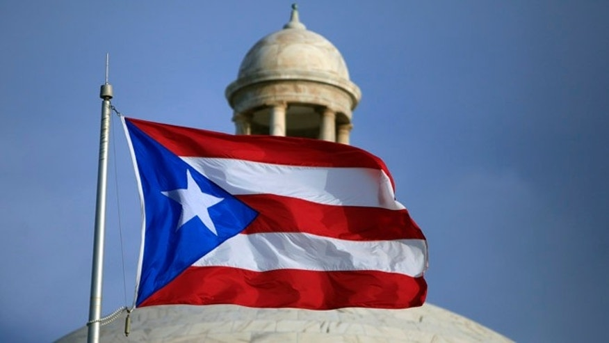 FILE - In this Wednesday, July 29, file 2015 photo, the Puerto Rican flag flies in front of Puerto Ricoâs Capitol as in San Juan, Puerto Rico. Legislators in Puerto Rico have approved on Monday, Feb. 15, 2016, a last-minute bill needed to finalize a deal to restructure the U.S. territory's heavily indebted public power company. (AP Photo/Ricardo Arduengo, File)
