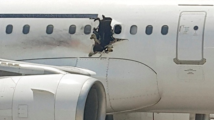 FILE: A hole is photographed in a plane operated by Daallo Airlines as it sits on the runway of the airport in Mogadishu, Somalia. Abdullahi Abdisalam Borleh boarded the plane on Feb. 2 with a bomb which exploded at 11,000 feet.