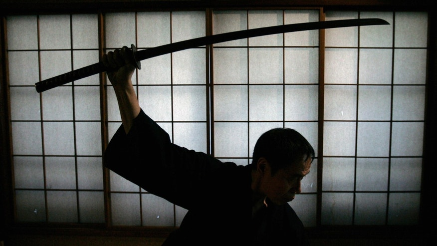 Japanese man holds a samurai sword. (Reuters)