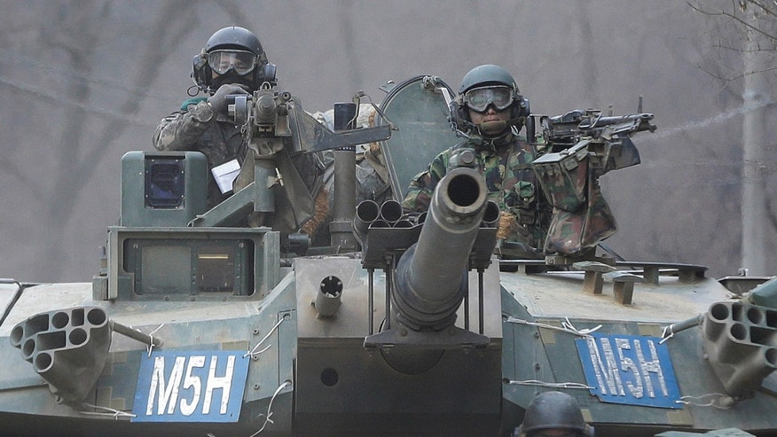 FEb. 19, 2016: South Korean army soldiers ride a K-1 tank during the annual exercise in Paju, near the border with North Korea.