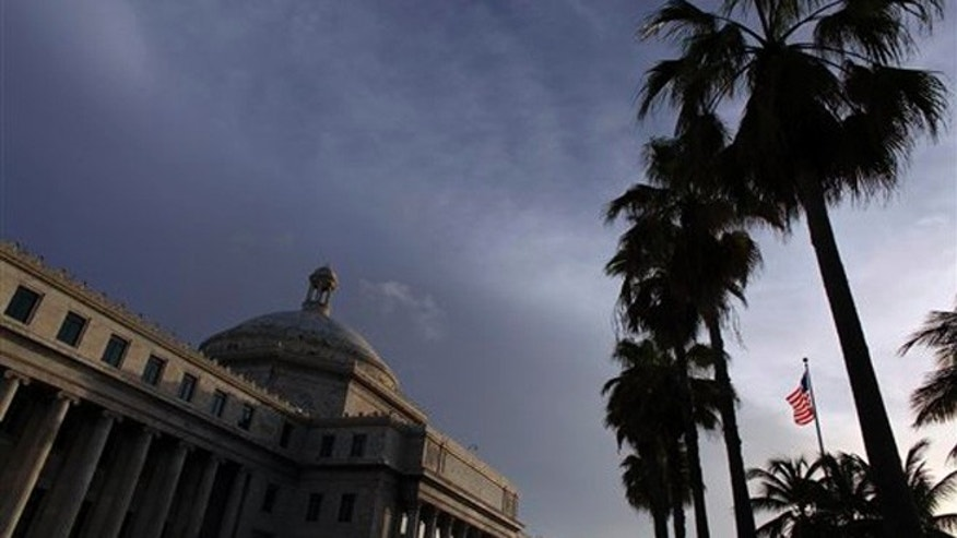 FILE - In this July 29, 2015 file photo, the U.S. flag flies in front of Puerto Ricoâs Capitol in San Juan, Puerto Rico. Plans to create a powerful fiscal control board to help stabilize the U.S. territory's finances and appease bondholders amid an economic crisis have been derailed. On Thursday, Nov. 12, 2015, legislators approved the measure but only after making amendments that strip the board of most of its powers. The Senate will review the amended bill again before it is presented to the islandâs governor. (AP Photo/Ricardo Arduengo, File)