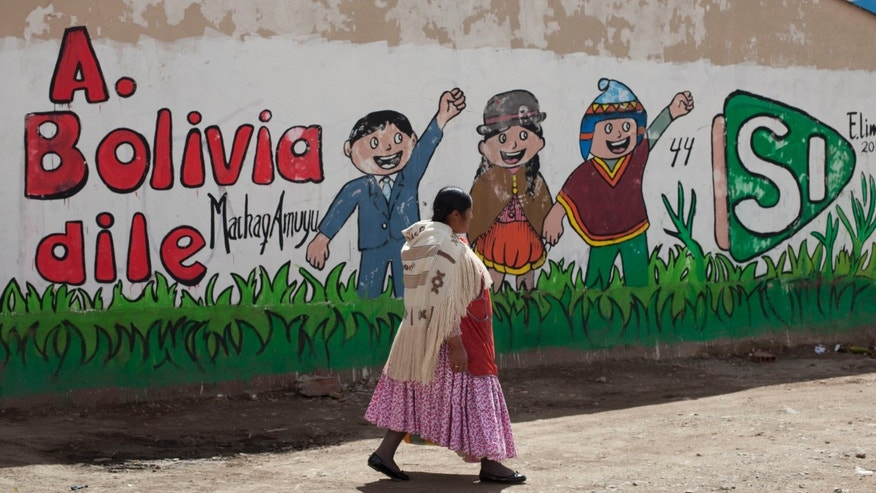 "An Aymara woman walks past a mural that reads in Spanish ""Tell Bolivia Yes,"" in favor of President Evo Morales, in El Alto, Bolivia, Saturday, Feb. 20, 2016. Polls indicate voters are about evenly split, with some 15 percent undecided, on Sunday's referendum on whether to amend the constitution so Morales can run in 2019 for a fourth consecutive term. (AP Photo/Juan Karita)"