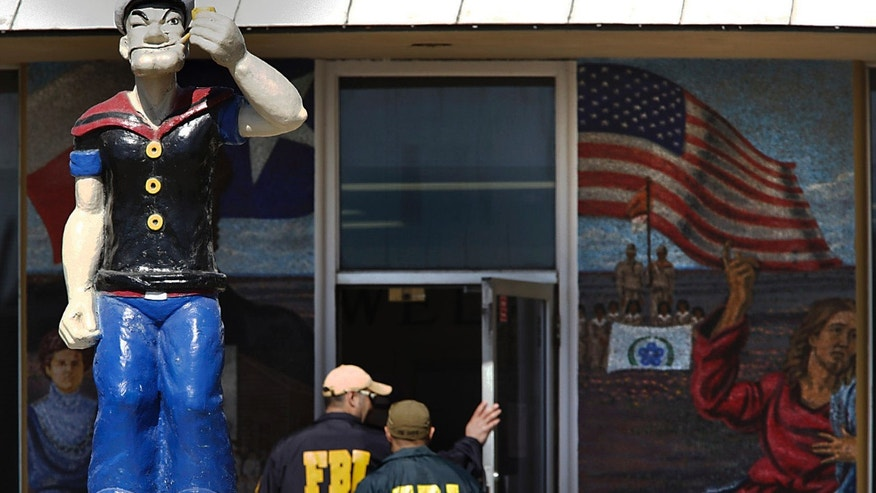 "FBI agents walk past a statue of Popeye, the mascot of Crystal City, Texas, as they enter city hall to seize computers and documents on Thursday, Feb. 4, 2016. Almost every top official in the South Texas town was arrested Thursday under a federal indictment accusing them of taking bribes from contractors and sending city workers to help an illegal gambling operator nicknamed ""Mr. T."" The town was once billed as the ""Spinach Capital of the World."" (Bob Owen/The San Antonio Express-News via AP) RUMBO DE SAN ANTONIO OUT; NO SALES; MANDATORY CREDIT"