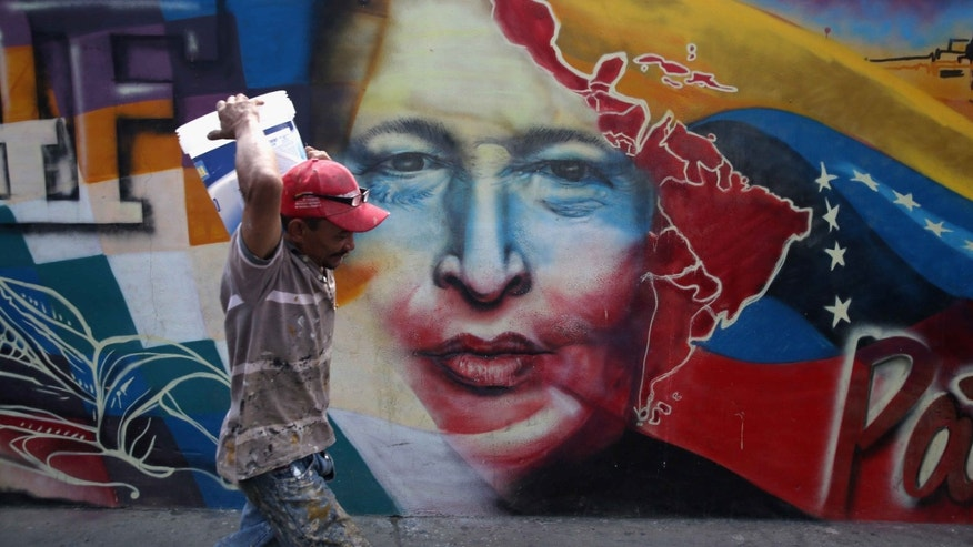 CARACAS, VENEZUELA - MARCH 04:  A worker passes a mural of Hugo Chavez at the military barracks where the former Venezuelan president is entombed on March 4, 2014 in Caracas, Venezuela. Workers made last minute preparations for Wednesday's ceremony marking the first anniversary of Chavez' death on March 5, 2013. The anniversary has been marred by three weeks protests against the government of Chavez' chosen successor Nicolas Maduro. (Photo by John Moore/Getty Images)