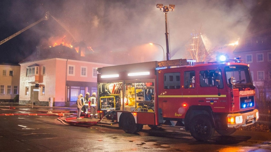 Feb. 21, 2016: A fire engine stands in front of a burning building in Bautzen, eastern Germany. The fire damaged a former hotel that was being converted into a refugee home and two people were detained after hindering firefighters' work, police said (Rico Loeb/dpa via AP)