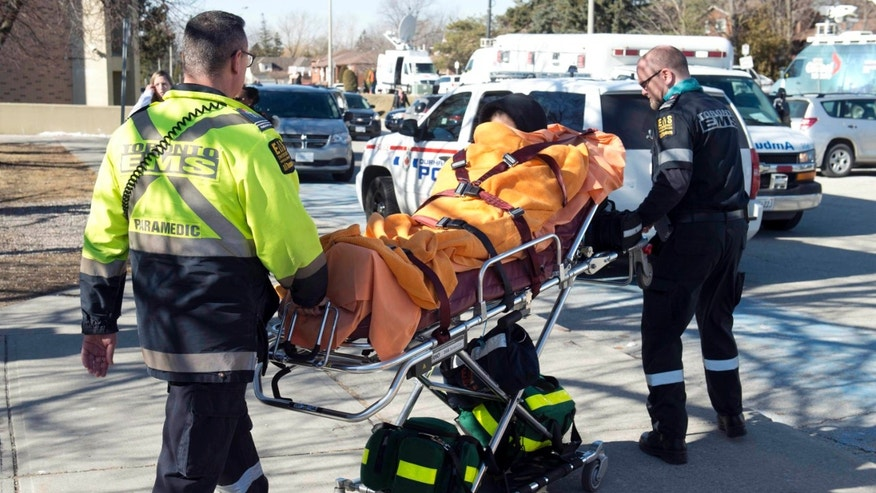 Feb. 24, 2016: An unidentified victim is taken away on a stretcher by emergency personnel remove following a stabbing incident at Dunbarton High School in Pickering, Ontario.
