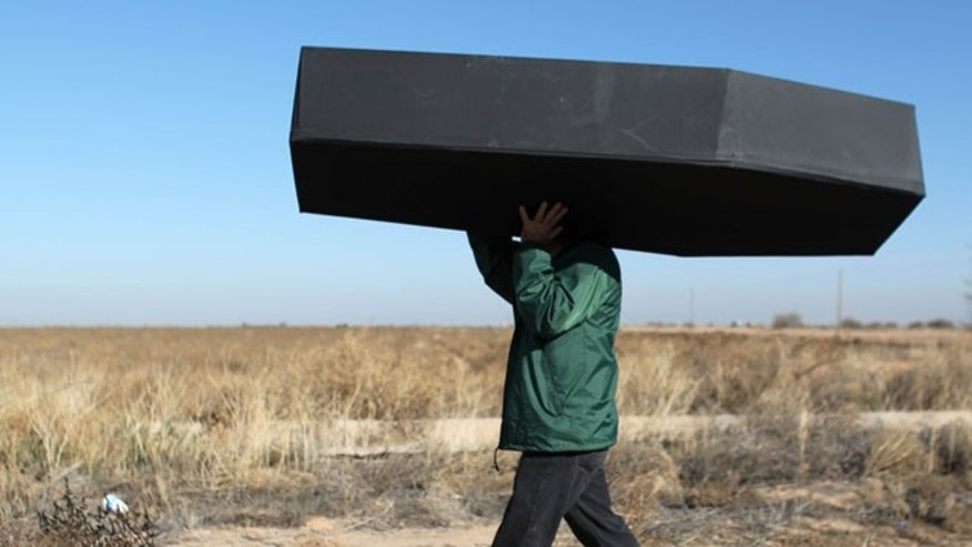 A demonstrator carries a mock coffin outside the ICE detention center in Eloy, Ariz.