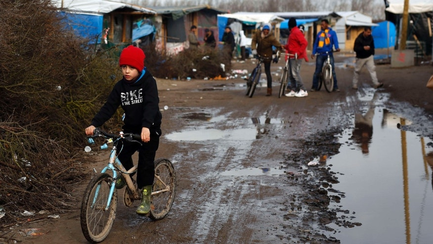 Feb. 25, 2016: A child rides his bicycle in a makeshift camp for migrants near Calais, France.