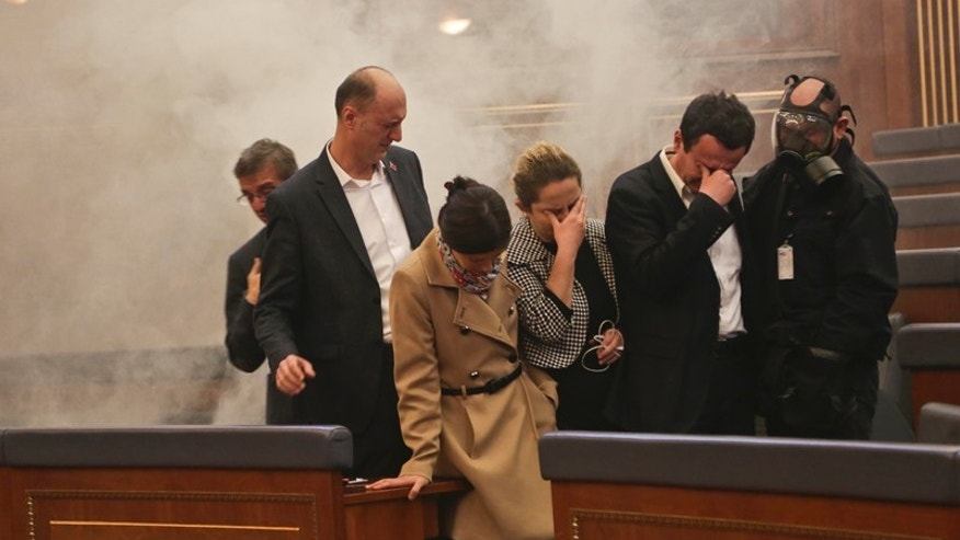 Feb. 26, 2016: Opposition lawmakers cover their eyes as smoke fills the auditorium of the Kosovo assembly after they released tear gas canisters disrupting a parliamentary session in Kosovo capital Pristina.