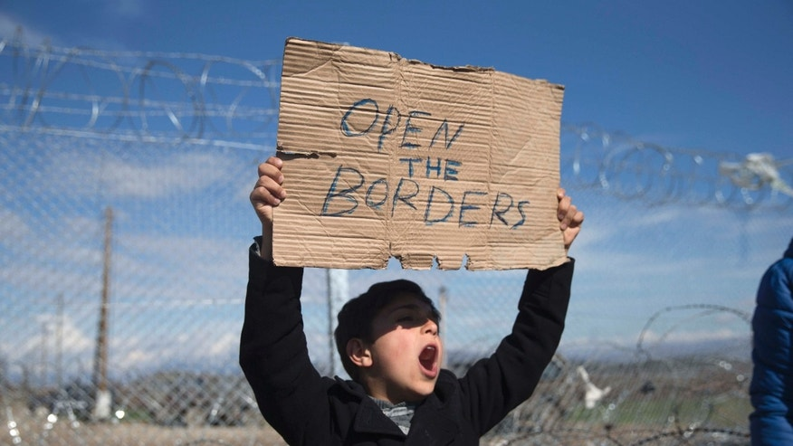 Feb. 27, 2016: A boy shouts slogans as he holds a placard during a protest by refugees and migrants in front of the wire fence that separates the Greek side from the Macedonian one at the northern Greek border station of Idomeni.