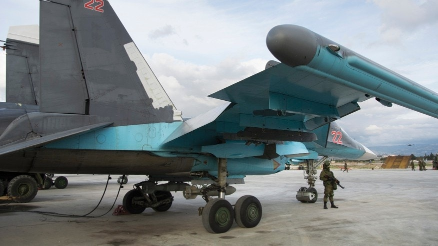 Jan. 20, 2016: A Russian soldier stands guard next to a Su-34 bomber at Hemeimeem air base in Syria.