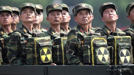 FILE - In this July 27, 2013, file photo, North Korean soldiers turn and look towards their leader Kim Jong Un as they carry packs marked with the nuclear symbol as they parade during a ceremony marking the 60th anniversary of the Korean War armistice in Pyongyang, North Korea. North Korea claims to have tested its first H-bomb on Jan. 6, the day after the Department of Defense report came out. That claim has been disputed, but there is no doubt it has some nuclear weapons' capability and its technicians are hard at work improving the nuclear weapons in quantity and quality. (AP Photo/Wong Maye-E, File)
