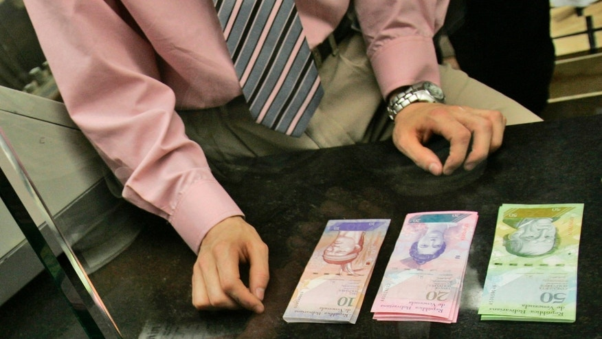 A bank worker changes old Bolivares for Venezuela's new currency in Caracas, Venezuela.