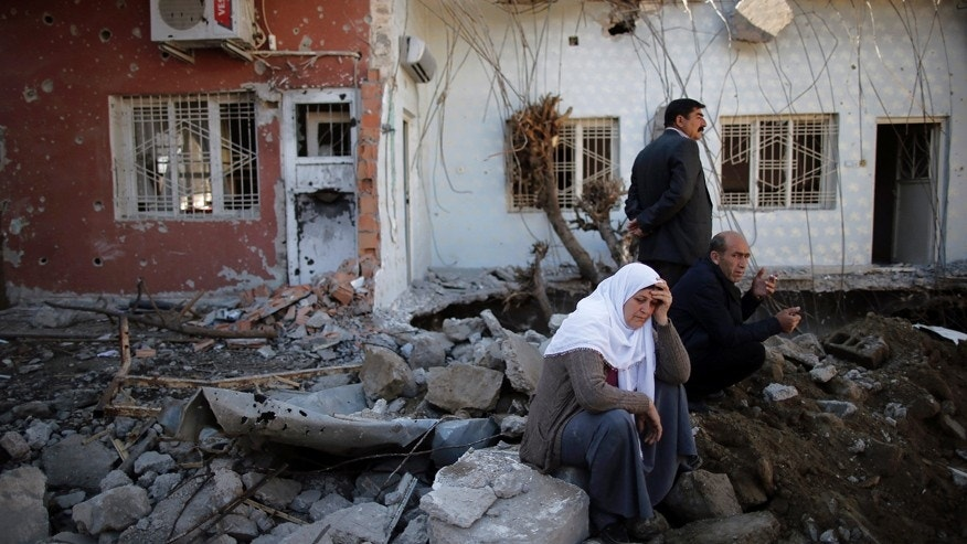 March 2, 2016: People look at their ruined houses in Cizre, Turkey.