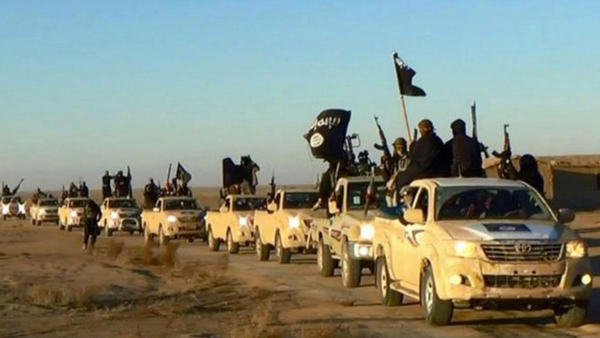FILE - In this undated photo released online in the summer of 2014 on a militant social media account, which has been verified and is consistent with other AP reporting, ISIS militants hold up their weapons and wave its flags on their vehicles in a convoy on a road leading to Iraq, in Raqqa, Syria.
