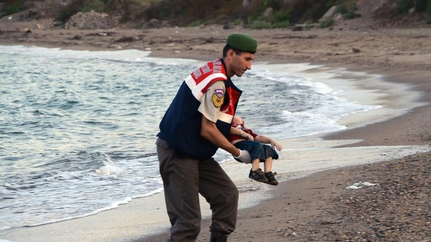 A paramilitary police officer carries the lifeless body of Aylan Kurdi, 3, after refugee boats capsized off the Turkish resort of Bodrum in September.