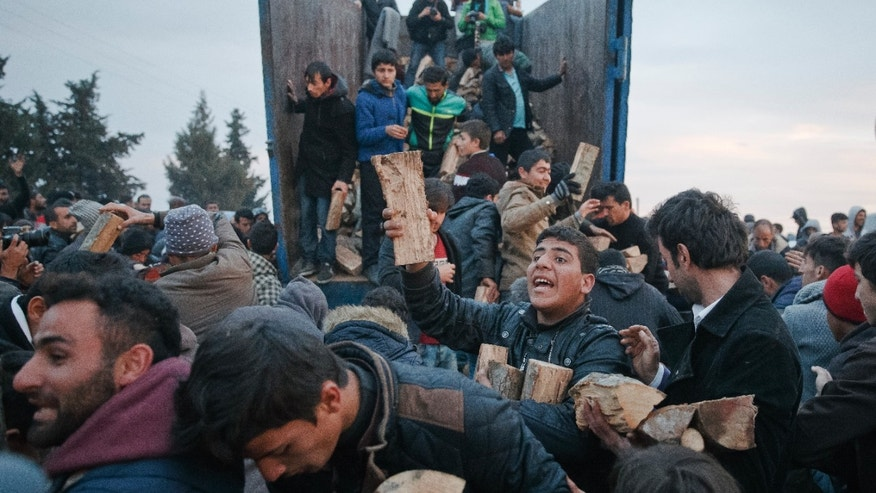 Migrants mob a truck bringing donated firewood at the northern Greek border station of Idomeni.
