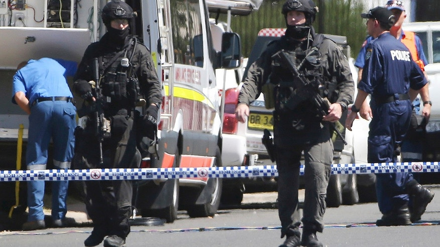 March 7, 2016: Police Tactical Group officers walk on a cordoned off street of an industrial section of Ingleburn, in suburban Sydney, as police respond to a shooting. (AP Photo/Rick Rycroft)
