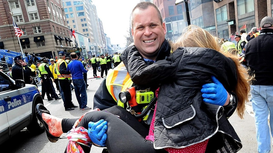 Victoria McGrath is carried in the arms of a firefighter after the Boston Marathon bombing.