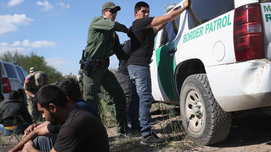 A Border Patrol agent body searches an undocumented immigrant on December 7, 2015 near Rio Grande, Texas.