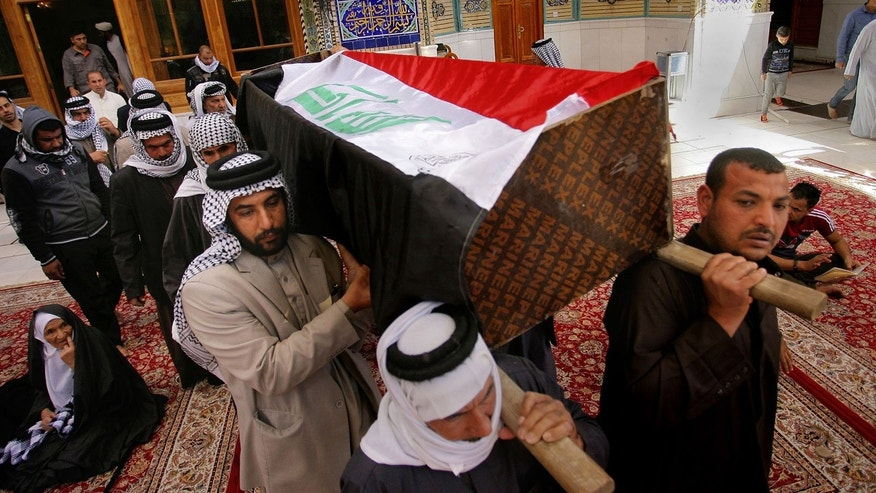 March 7, 2016: Mourners carry an Iraqi flag-draped coffin of bomb victim Rasul Kadim, 24, during his funeral procession at the shrine of Imam Ali in Najaf, 100 miles south of Baghdad, Iraq.  (AP Photo/Anmar Khalil)