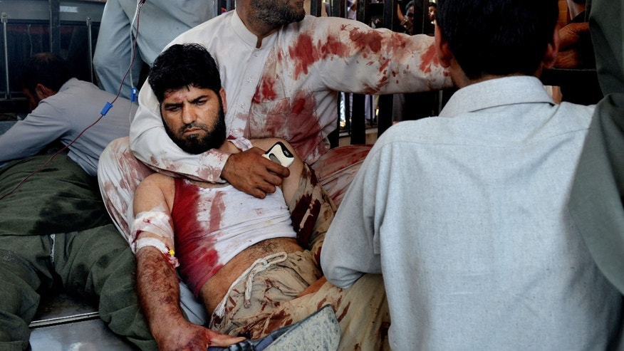 Volunteers carry an injured man to a hospital in Peshawar, Pakistan.