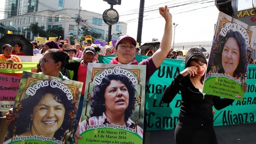 Women carry images of slain environmental activist Berta Caceres during the commemoration of International Women's Day in Tegucigalpa, Honduras, Tuesday, March 8, 2016. Caceres, a Lenca Indian activist who won the 2015 Goldman Environmental Prize for her role in fighting a dam project was killed by unknown assailants on March 3, 2016. She had previously complained of receiving death threats from police, soldiers and local landowners because of her work. (AP Photo/Fernando Antonio)
