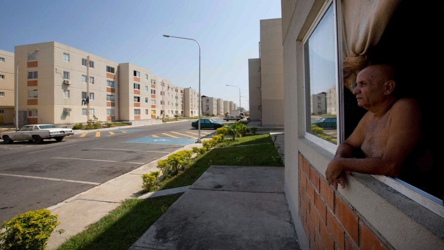 Resident Jose Manzanares looks out his government-assigned home, in the Socialist City of Hugo Chavez.