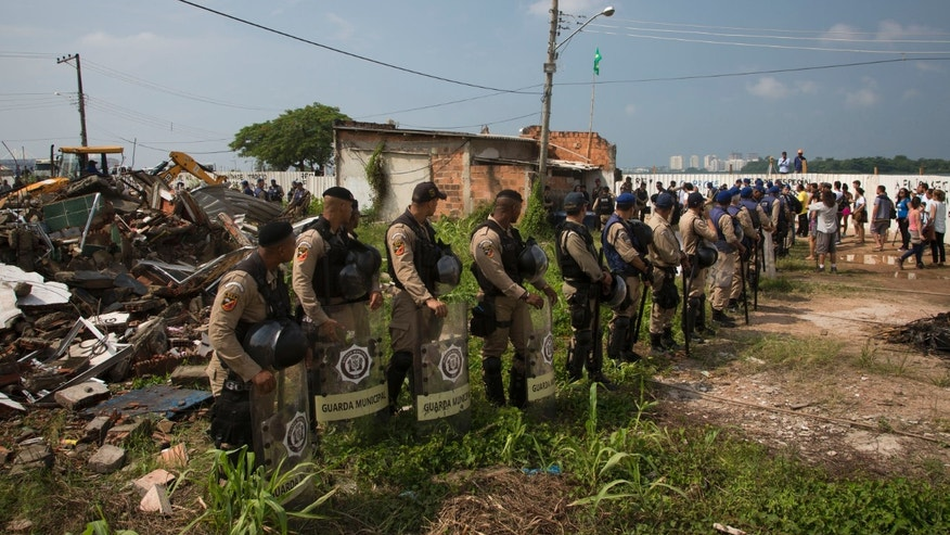 Police officers stand guard during a demolition of the Vila Autodromo slum, in Rio de Janeiro, March 8, 2016.
