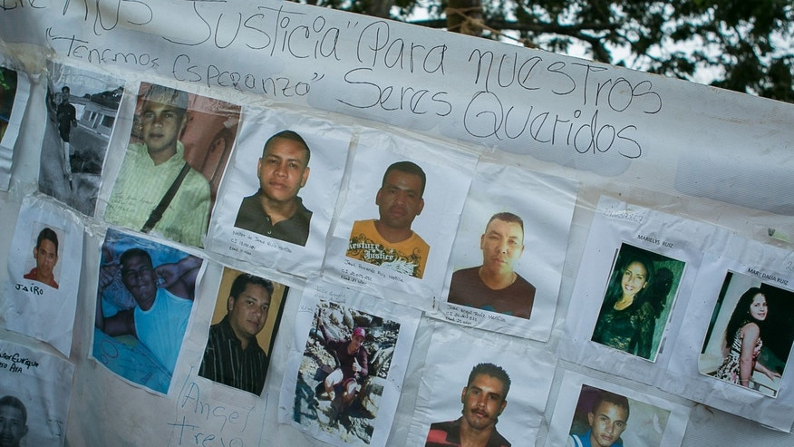 A banner with photos of several missing miners hangs on a tree near Tumeremo, Venezuela, Tuesday, March 8, 2016.