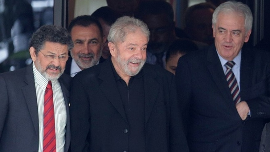 Brazilâs former President Luiz Inacio Lula da Silva, center, smiles as he leaves a breakfast with senators of the government's allied base, in Brasilia, Brazil, Wednesday, March 9, 2016. (AP Photo/Eraldo Peres)