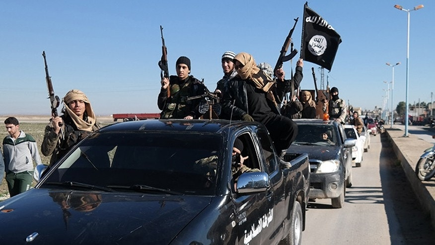 May 4, 2015: In this this file photo released on a militant website, which has been verified and is consistent with other AP reporting, Islamic State militants pass by a convoy in Tel Abyad, northeast Syria.