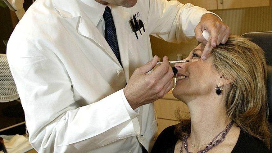 404141 01: Dr. Louis P. Bucky, M.D., F.A.C.S., injects Botox into the face of Betsy Rubenstone, 50, from the Philadelphia area, April 18, 2002 at the Plastic & Reconstructive Surgery Center at the Pennsylvania Hospital in Philadelphia. When injected into facial muscles Botox or botulinum toxin eliminates wrinkles by weakening or paralyzing the muscles which keeps them from contracting. The effect lasted for up to three months. The U.S. Food and Drug Administration (FDA) approved cosmetic use of Botox April 15, 2002. (Photo by Don Murray/Getty Images)