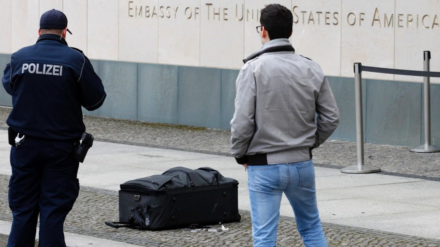 March 11, 2016: Police officers photograph a suitcase in front of the US embassy in Berlin, Germany.  A 23-year-old German man is in custody after falsely claiming to have a bomb inside a suitcase he was trying to bring into the U.S. Embassy, police said Friday. (AP Photo/Ferdinand Ostrop)