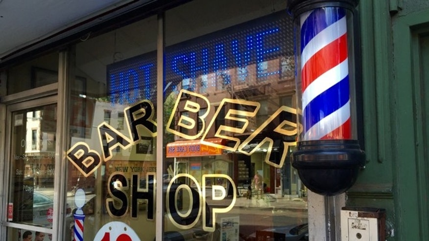 The exterior glass facade of a ground floor commercial storefront Barber Shop with a traditional barbers pole - Park Slope, Brooklyn, NYC September 25, 2015