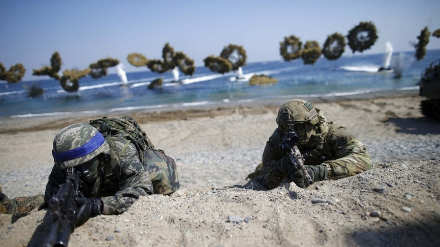 South Korean (blue headbands) and U.S. Marines take positions as amphibious assault vehicles of the South Korean Marine Corps fire smoke bombs during a U.S.-South Korea joint landing operation drill in Pohang, South Korea