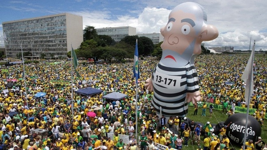 Demonstrators demand the impeachment of Brazil's President Dilma Rousseff during a rally where a large inflatable doll of former President Luiz Inacio Lula da Silva stands in prison garb in Brasilia, Brazil, Sunday, March 13, 2016. The corruption scandal at the state-run oil giant Petrobras has ensnared key figures from Rousseffâs Workersâ Party, including her predecessor and mentor, Lula da Silva, as well as members of opposition parties. (AP Photo/Eraldo Peres)