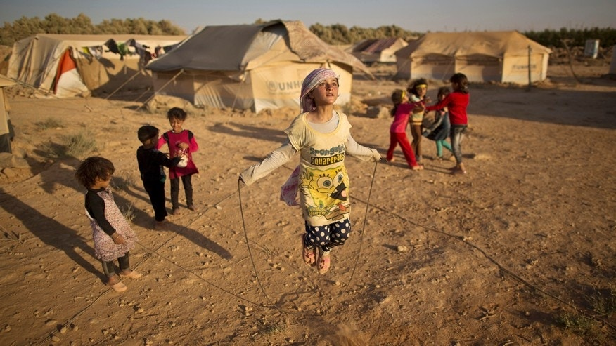 July 19, 2015: Syrian refugee girl, Zubaida Faisal, 10, skips a rope while she and other children play near their tents at an informal tented settlement near the Syrian border on the outskirts of Mafraq, Jordan.