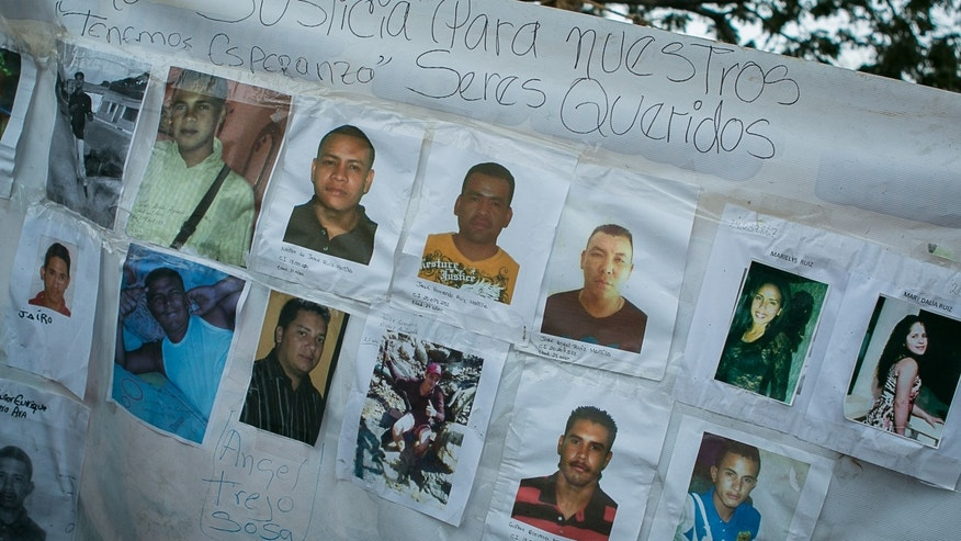 A banner with photos of several missing miners hangs on a tree near Tumeremo, Venezuela, March 8, 2016.