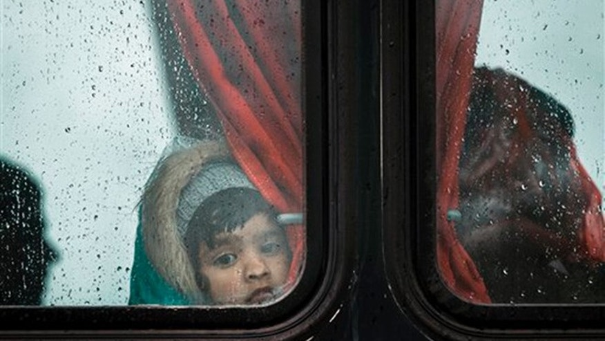 A migrant girl presses her nose agains a bus window during a rainfall on a road, north of Idomeni, Greece, Tuesday, March 15, 2016. Hundreds of migrants and refugees walked out Monday of an overcrowded camp on the Greek-Macedonian border Monday, determined to use a dangerous crossing to head north but were returned to Greece.(AP Photo/Vadim Ghirda)