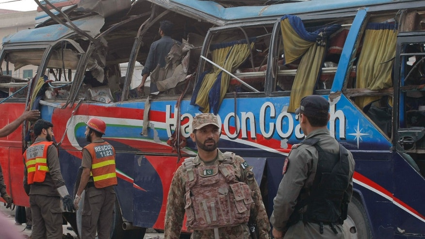 March 16, 2016: Pakistani security personnel examine a bus following a bomb blast in Peshawar, Pakistan.