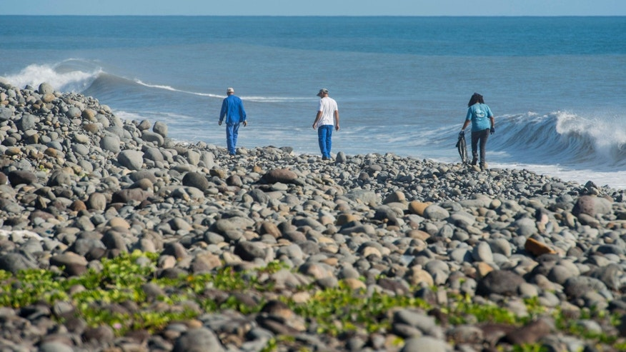 FILE - In this Aug. 10, 2015 photo, municipal workers search Reunion Island beaches where expected debris of the missing Malaysia Airlines Flight 370 could be washed up onto the shore near Saint-Andre, Reunion island.
