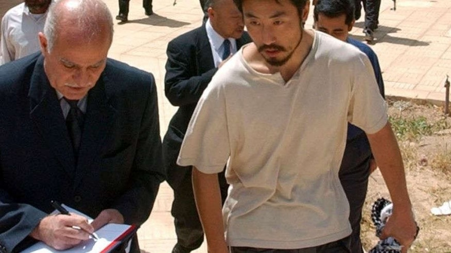 FILE - In this April 17, 2004 file photo, Japanese freelance journalist Jumpei Yasuda, right, is escorted after being released at Umm Al-Qura mosque in Baghdad, Iraq.