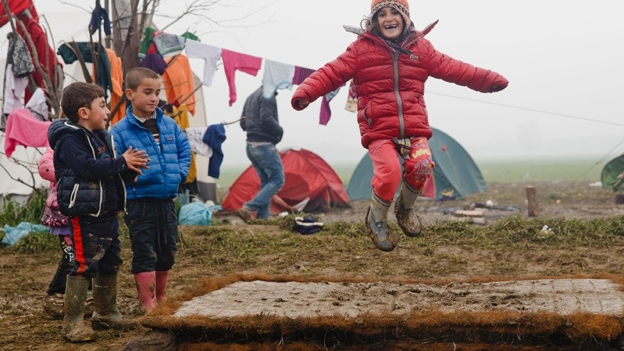 March 18, 2016: Migrant children play jumping on a muddy mattress at the northern Greek border point of Idomeni, Greece.