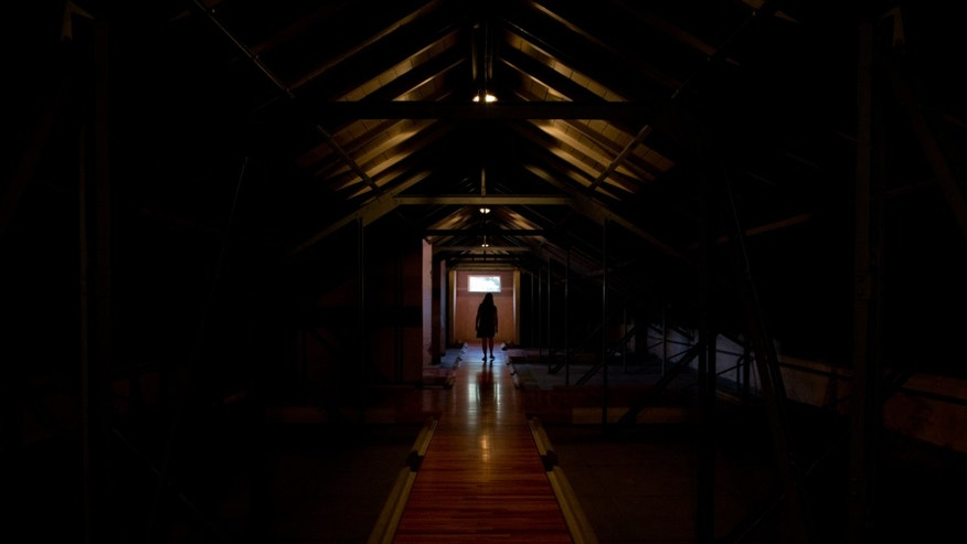 "A woman stands in an attic known in Spanish as ""Capucha"" or hood in English, a place where detainees were hooded and believed to be tortured during the country's 1976-1983 military dictatorship, at the former Argentine Navy School of Mechanics, in Buenos Aires, Argentina, Wednesday, March 16, 2016. U.S. President Barack Obama will move to declassify U.S. military and intelligence records related to Argentina's ""Dirty War,"" the White House said Thursday, March 17, aiming to bring closure to questions of U.S. involvement in a notorious chapter in Argentina's history. The Argentine Navy School of Mechanics was used by the military government as a torture and killing center during the military dictatorship and is now a center for the remembrance of the victims and the promotion and defense of human rights. (AP Photo/Natacha Pisarenko)"