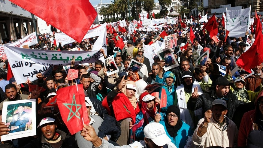 March 13, 2016: Protesters hold portraits of Morocco's King Mohammed VI and the Moroccan flag as they chant slogans during a rally, in Rabat, Morocco.