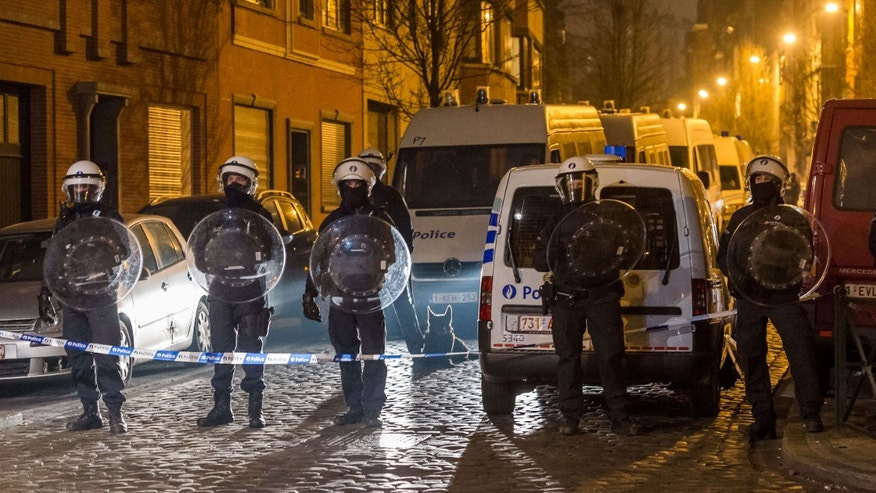 March 18, 2016: Police officers secure a street during a raid in the Molenbeek neighborhood of Brussels, Belgium.